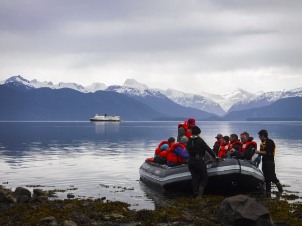 Guests entering their skiff from shore to go back to their small ship cruise in Alaska.