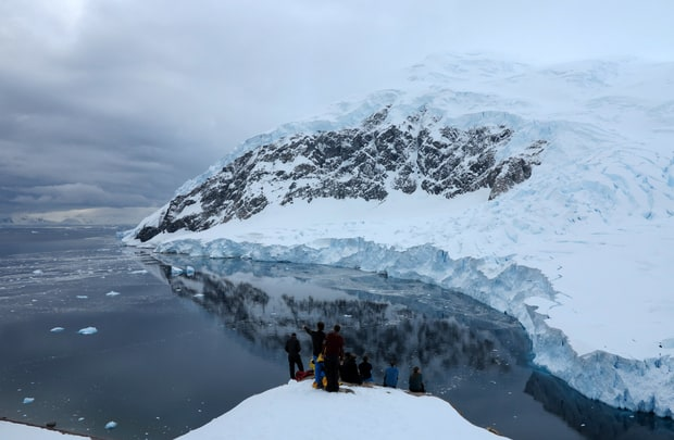 Guests from a small ship over looking the bay at Neko Harbor in Antarctica.