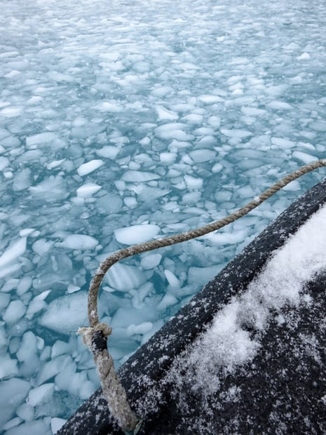 Brash Ice see up against  and in front of the bow of a small cruise expedition ship in Antarctica.
