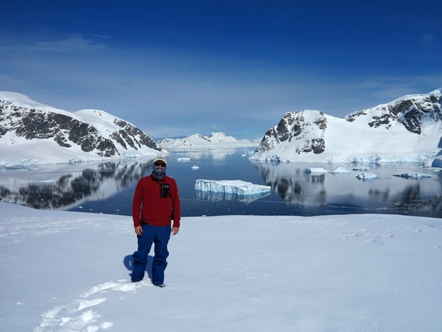 Guest from small ship smiling in front of icebergs at Danco Island Antarctica.