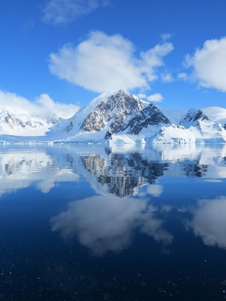 View of mountain reflections at Wilhelmina Bay from a small ship in Antarctica.