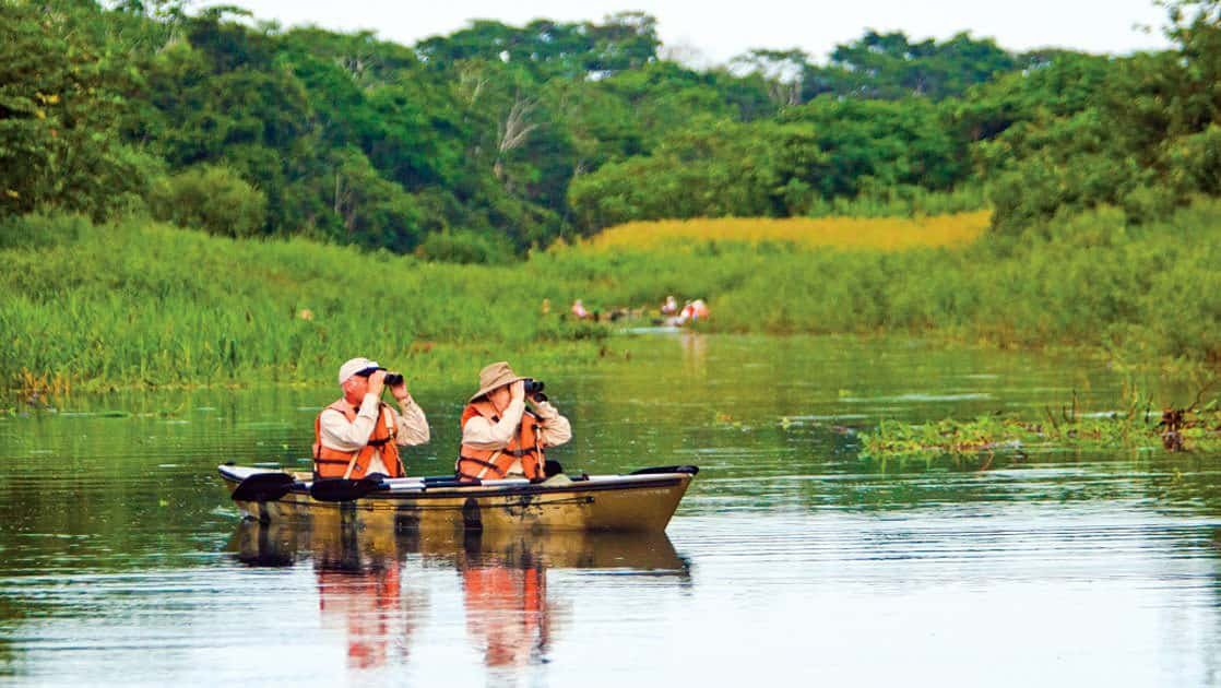 Couple looking through binoculars in a canoe on an Amazon cruise