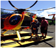 Honeymoon travelers in front of yellow and orange helicopter