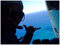 Traveler giving hang-loose sign in helicopter over water