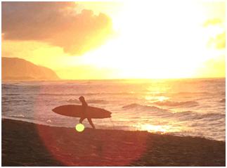 Surfer silhouette walking along Hawaiian beach with sun setting