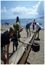 People picking up a large outrigger canoe