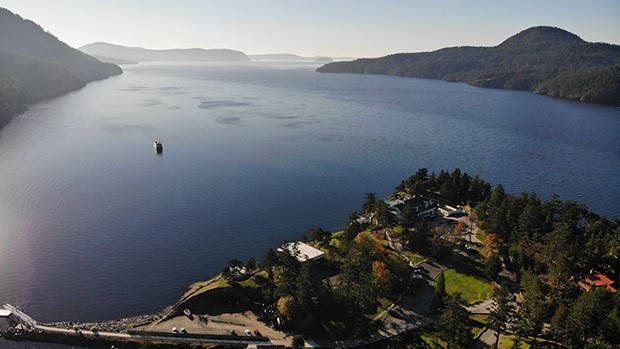 A view from a vista point of a Pacific Northwest body of water with green mountains jetting into the water, seen from a cruise to the San Juan Islands.