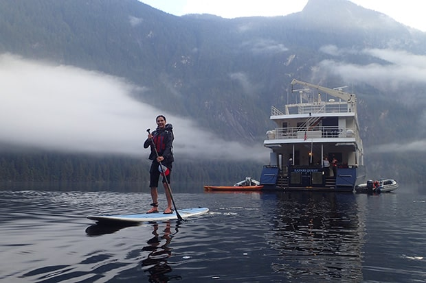 A stand-up paddle boarder floats in front of the Safari Quest on Alaska's Inside Passage & San Juans Cruise.