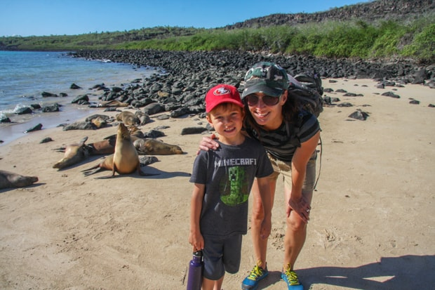 Family in front of seals on the beach in Galapagos.