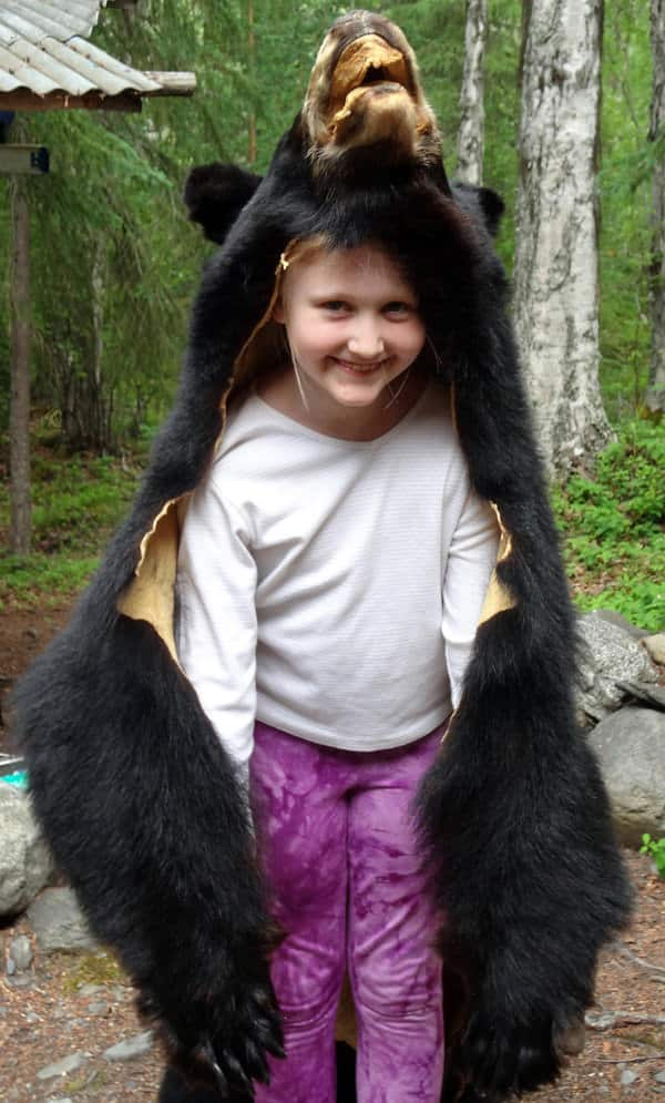 Happy small child wearing a black bear skin in Alaska.