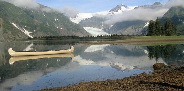 Kenai Glacier Lodge Canoe on a glassy lake with Pederson Glacier in the background.