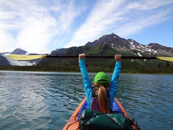 Kayaker holding up paddle while kayaking on Shilak Lake.