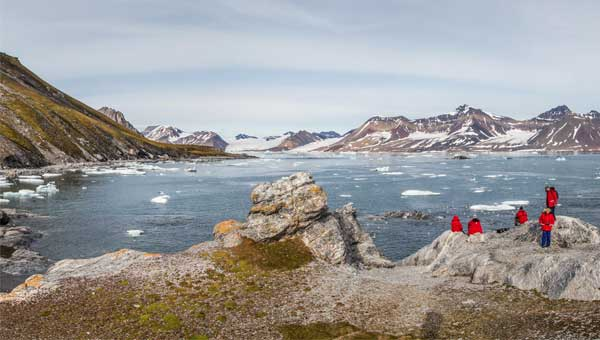 Arctic cruise travelers stand on top of a rocky hillside overlooking a bay with icebergs, with snow-touched mountains in the distance.