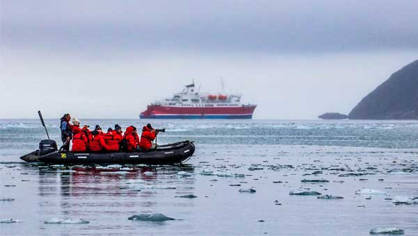 Arctic cruise travelers in red jackets take photographs of iceberg bits in the water on a Zodiac cruise to the Arctic Circle, with a small polar ship in the background.