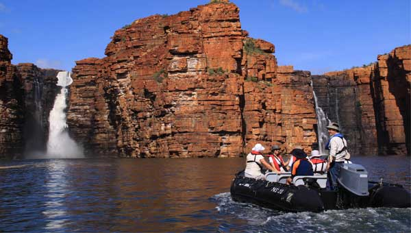 Travelers in a skiff explore red cliffs and a towering waterfall in the Kimberley of Australia