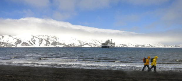 Small expedition ship in Antarctica with guests walking on land.