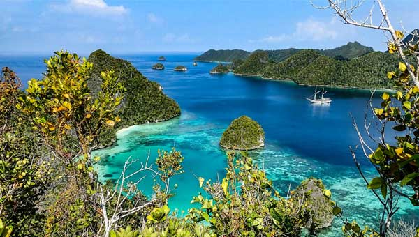 A remote bay in Raja Ampat Indonesia with a white, masted small cruise ship anchored at the shore.