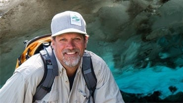 adventuresmith explorations founder and president todd smith smiling in front of a brown and blue glacier in alaska