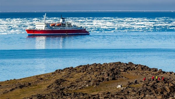 A red-hulled Arctic expedition ship in calm icy waters near a rocky brown shore.