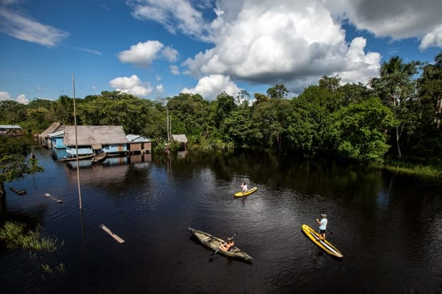 A couple stand-up paddleboarding in the Peruvian Amazon.
