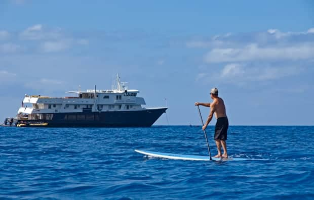 A man, stand-up paddleboarding, in front of a small ship.