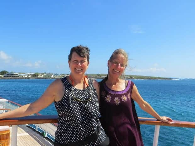 Two women smiling on deck of their small ship cruise in the Galapagos.