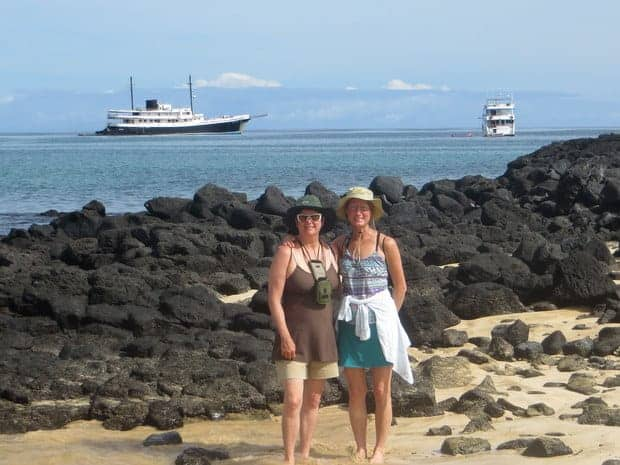 Two women smiling on the beach in the Galapagos with their small cruise ship in the background.