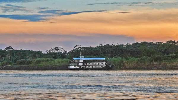 A small riverboat cruise ship is seen near the shore of the Amazon River in Peru at sunset