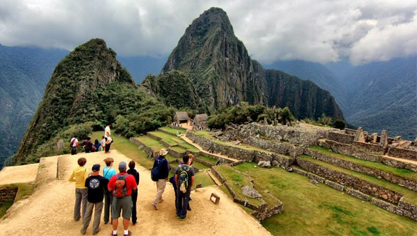 A small guided group gathers on a dirt path in the foreground of the Machu Picchu ruins and the towering Huayna Picchu