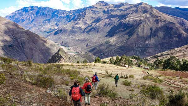 A group of hikers on a Peru trek down to Pisaq seen on a grassy hillside with big brown mountains in the background.