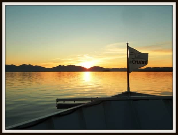 The Un-Cruise flag waving from the bow of the small ship cruise at sunset with the Alaskan mountains.
