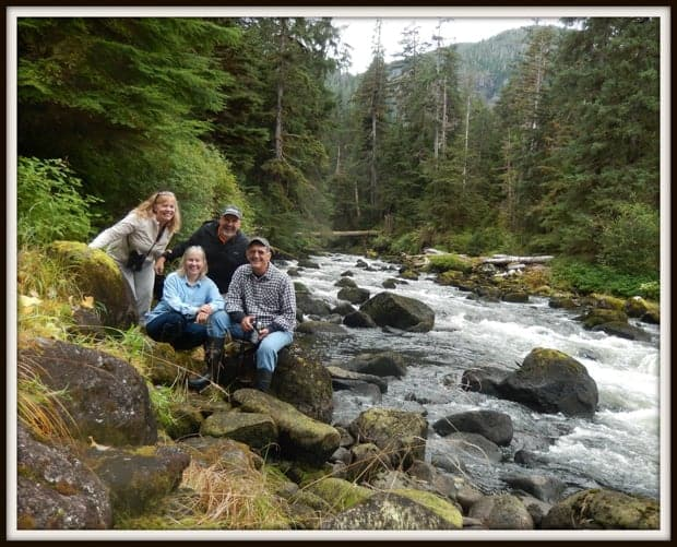 4 hikers sitting next to a river in the forest of Alaska.