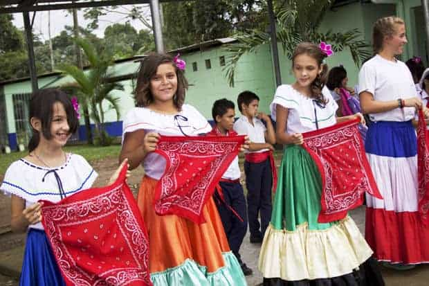 Young Costa Rican girls in colorful dresses with young boys behind them at a local school.