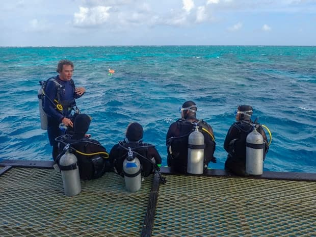 A SCUBA guide talks with a family of divers aboard a small ship