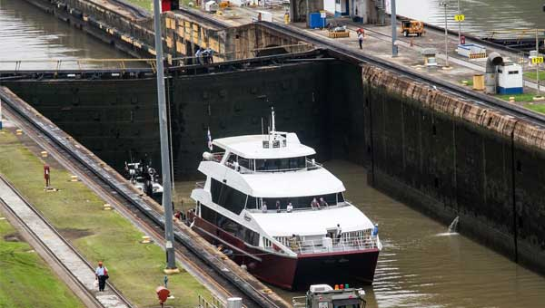 Small red-&-white ship travels through the Panama Canal on a cruise.