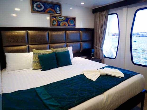 Inside view of a stateroom on the Alya of a king size bed and large panoramic windows.