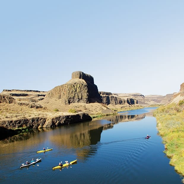 People kayaking on excursion in the Palouse River in Washington on a Pacific Northwest river cruise.