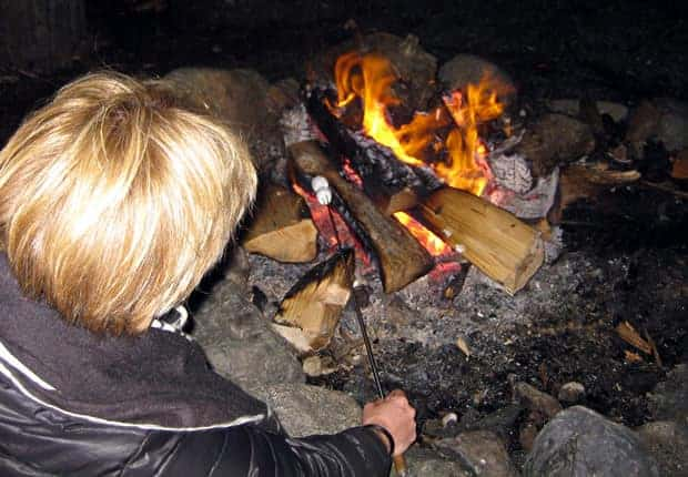 Traveler roasting marshmellows by the campfire at night.