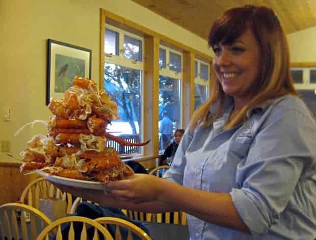 Happy travelers enjoying a large plate of Alaskan King Crab legs.