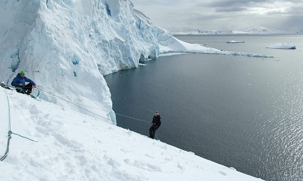 Guest from small ship cruise mountaineering and hiking up in the snow using a rope in Antarctica.