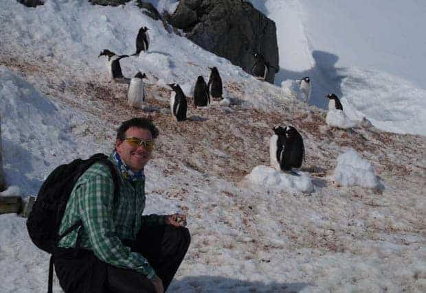 Guest from small ship cruise kneeling and smiling next to penguins on the snow in Antarctica.