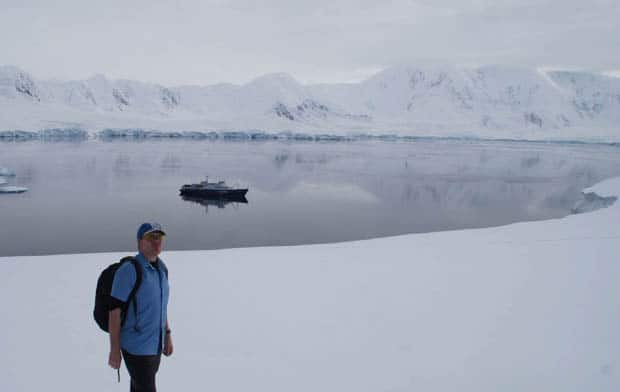 Guest in tshirt with snowy landscape in Antarctica will small ship cruise in background.