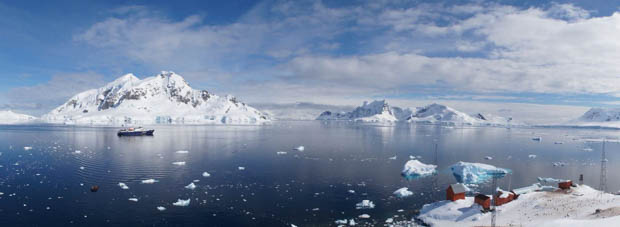 Panorama of small ship cruise in Antarctica with research station.
