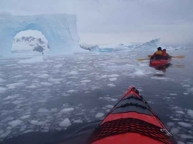 Small ship cruise guests on kayaking excursion in Antarctica close to icebergs and surrounded by ice in the water.