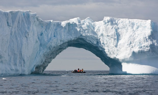 Skiff full of small cruise ship passengers underneath a large arch in the iceberg in Antarctica.