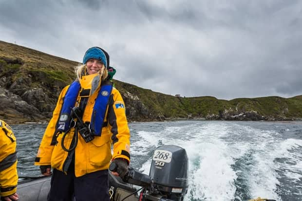 Guide from small cruise ship steering the skiff in Antarctica.