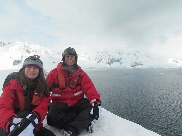 Two smiling small ship guests sitting on the snow in Antarctica.