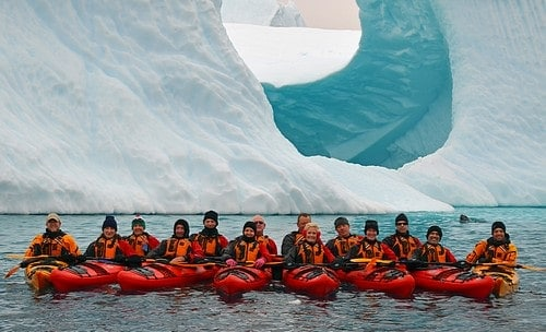 Small ship cruise guests on kayaking excursion lined up together in front of unique shaped and bright glacier.