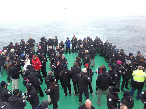 Guests aboard a small ship cruise on the deck together in Antarctica.