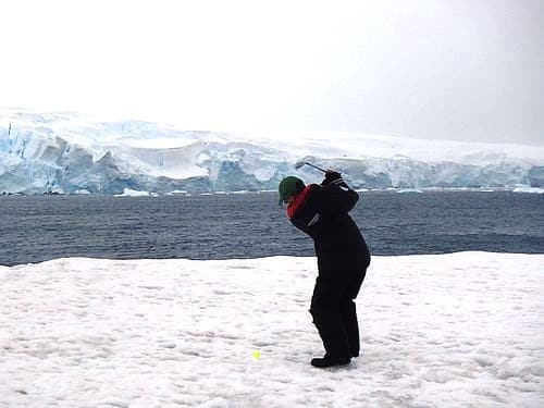 SMall ship passenger swinging a golf club on the snow in Antarctica.